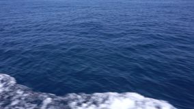 Clean sea water. Surface of deep sea water with foam stream, view from the ship, slow motion stock footage