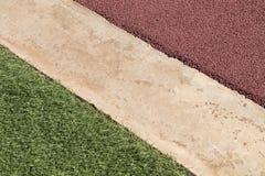 Surface en caoutchouc rouge de plancher de terrain de jeu de Wetpour à côté de béton et Photo libre de droits