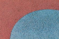 Surface en caoutchouc rouge et bleue colorée de plancher de terrain de jeu de Wetpour Images libres de droits