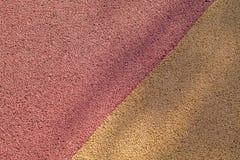 Surface en caoutchouc rouge et jaune colorée de plancher de terrain de jeu de Wetpour Images libres de droits
