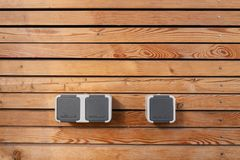 Surface of a freshly painted planking of a facade of wooden slats in the color mahogany and three 220 volt sockets royalty free stock photography