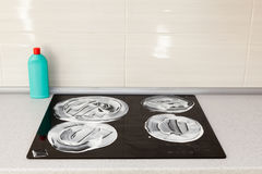 The surface of the induction stove is covered with a detergent. House cleaning - plastic bottles with detergents on kitchen tablet. Op on the background of Stock Photography