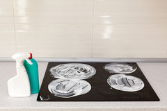 The surface of the induction stove is covered with a detergent. House cleaning - plastic bottles with detergents on kitchen tablet. Op on the background of Royalty Free Stock Photo