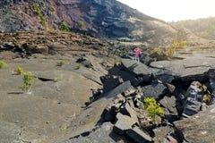 Surface l'explorant de jeune touriste féminin du cratère de volcan de Kilauea Iki avec la roche de émiettage de lave en parc nati Photos stock