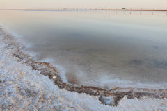 The surface of the  lake with very salty water. And wooden pillars and a salt crust on the surface of the desert and the lonely mountain Stock Images