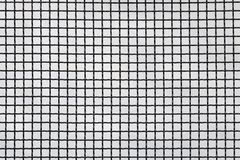 Surface of a latticed metal fence with squares elements in front of a wall made of wire. stock photo