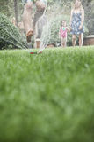 Surface level shot of father jumping through a sprinkler in the grass, mother and daughter watch in the background Royalty Free Stock Photo