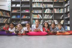 Happy schoolteacher lying with his school kids in a library. Surface level view of a happy schoolteacher lying with his school kids in a library against stock photo