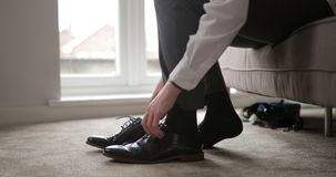 Man tying shoe laces. Surface level view of an unrecognisable male putting on his formal shoes and tying them stock video footage