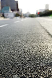 Empty Urban Road. Surface level wide angle view of an empty urban road in the afternoon hours. Very shallow depth of field Royalty Free Stock Image