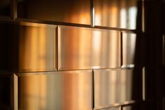 The surface of the mirror tiles. Wall of mirrored tiles with edges. Interior design with sunset lighting. Rows of mirror tiles. Abstraction of tiles with sharp royalty free stock photos