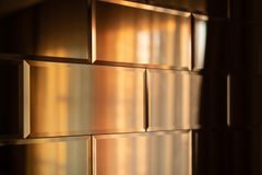 The surface of the mirror tiles. Wall of mirrored tiles with edges. Interior design with sunset lighting. Rows of mirror tiles. Abstraction of tiles with sharp stock photography