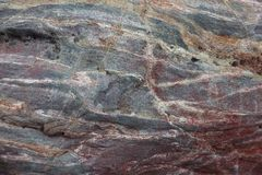 Surface of natural red stone as background. Surface of natural dark red stone (crimson quartzite porphyry) as background stock photo