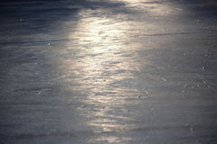 Surface of an outdoor ice rink replete with skate marks reflects the spring sun Stock Images