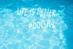 Surface of  pool water with quote life is better poolside royalty free stock photos