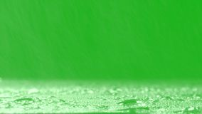Surface Rainstorm on green background. Realistic rain and water droplets with chroma key green screen background.