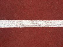 Surface rubberized running track. Surface perspective left to right of white line on the rubberized running track Stock Images
