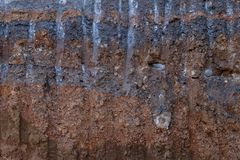 Surface soil layer under the road with digging trails. Close-up, background, surface, cross-section, soil, and stone under the paved road, with excavation tracks royalty free stock image