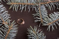 On the surface of the table is a golden ring. Around there are branches of blue spruce. On the surface of the table is a golden ring. Around there are branches Royalty Free Stock Image