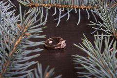 On the surface of the table is a golden ring. Around there are branches of blue spruce. Stock Image
