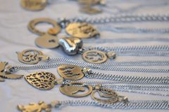 On the surface of the table are samples of women`s jewelry from metal and silver on chains. Fashionable jewelry on the neck for wo stock photo