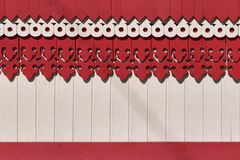 The surface of the wall or fence decorated with carved wooden boards patterns. And painted red and beige paint. Patterns in the form of holes, corners and royalty free stock photos