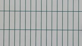 Surface of a welded wire fence with rectangular elements painted in green in front of a white wall. A welded wire fence with rectangular elements painted in Royalty Free Stock Images