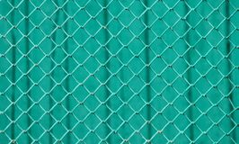 Surface of a wire netting with diamond-shaped elements painted in green in front of a green wall. Texture of a wire netting with diamond-shaped elements painted Royalty Free Stock Image