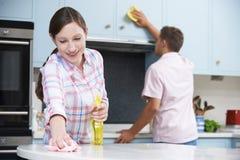 Surfaces et placards de cuisine de nettoyage de couples ensemble photos stock