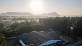 Animal livestock Farm housing in rural ranch. Surfaces on Livestock house, land and Cattle Farm in rural in Thailand with sunrise, fog and mountain background stock photos