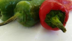 Surfaceslow-movimiento del agua del goteo de la pimienta roja y verde almacen de metraje de vídeo