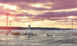 Surfacez sur l'entretien avant le vol à l'aéroport un coucher du soleil Image stock