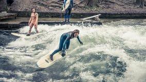 Surfar em Munich em Englischer Garten é perigoso mas possível: em um canal que cruza a paridade fotos de stock
