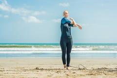 Surfare för ung kvinna som värmer upp på stranden, innan att surfa royaltyfri foto