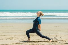 Surfare för ung kvinna som värmer upp på stranden, innan att surfa arkivfoton