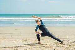 Surfare för ung kvinna som värmer upp på stranden, innan att surfa arkivbild