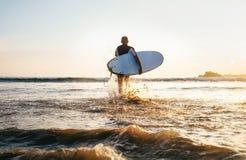 Surfare f?r ung man som tar surfingbr?dan och kommer med det l?nga br?nningbr?det till v?gor p? bakgrunden f?r aftonsolnedg?nghim arkivbild