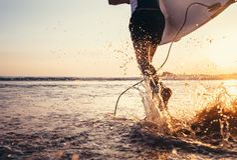 Surfare för ung man som tar surfingbrädan och spring med det långa bränningbrädet till vågor på bakgrunden för aftonsolnedgånghim royaltyfri bild