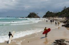 Surfare går i stranden av Byron Bay Arkivfoto