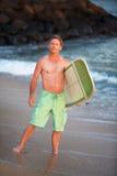 Surfare i gröna kortslutningar med surfingbrädan Fotografering för Bildbyråer