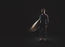 Surfare med bränningbrädet på svart bakgrund Arkivfoto