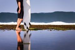 Surfare med surfingbrädan på en kustlinje Arkivbilder