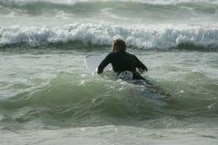 Surfare med surfingbrädan på stranden på havet fotografering för bildbyråer