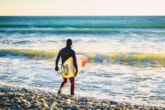 Surfare med surfingbrädan på stranden på solnedgången eller soluppgång Surfare- och havvågor Royaltyfri Fotografi