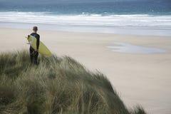 Surfare med surfingbrädan på stranden som ser havet royaltyfria foton
