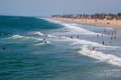 Surfare och badare längs Huntington Beachen royaltyfri bild
