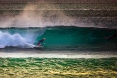 Surfare på blå havvåg i Bali Arkivfoto