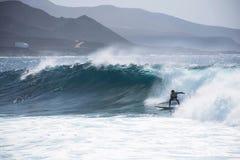 Surfare på stor våg med berg på bakgrunden Arkivfoto