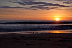Surfare på stranden av Santa Teresa på solnedgången/Costa Rica Arkivfoto