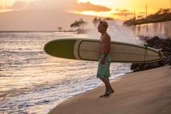 Surfare på stranden på solnedgången Arkivfoton